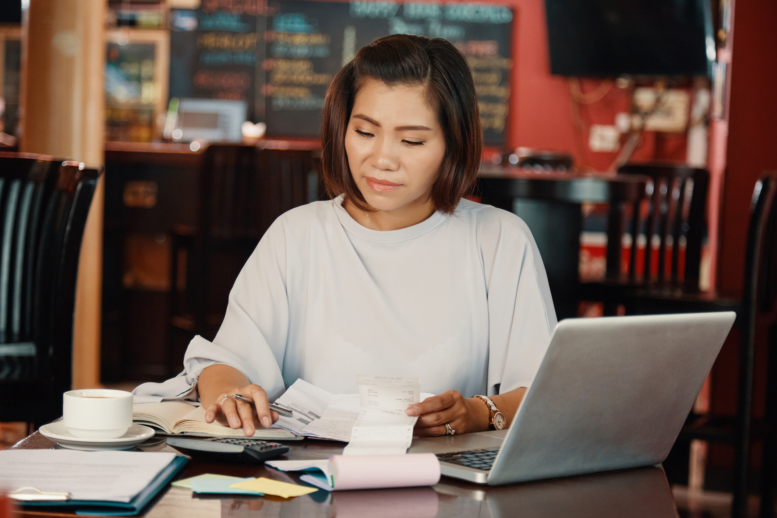 Woman calculating budget for her restaurant