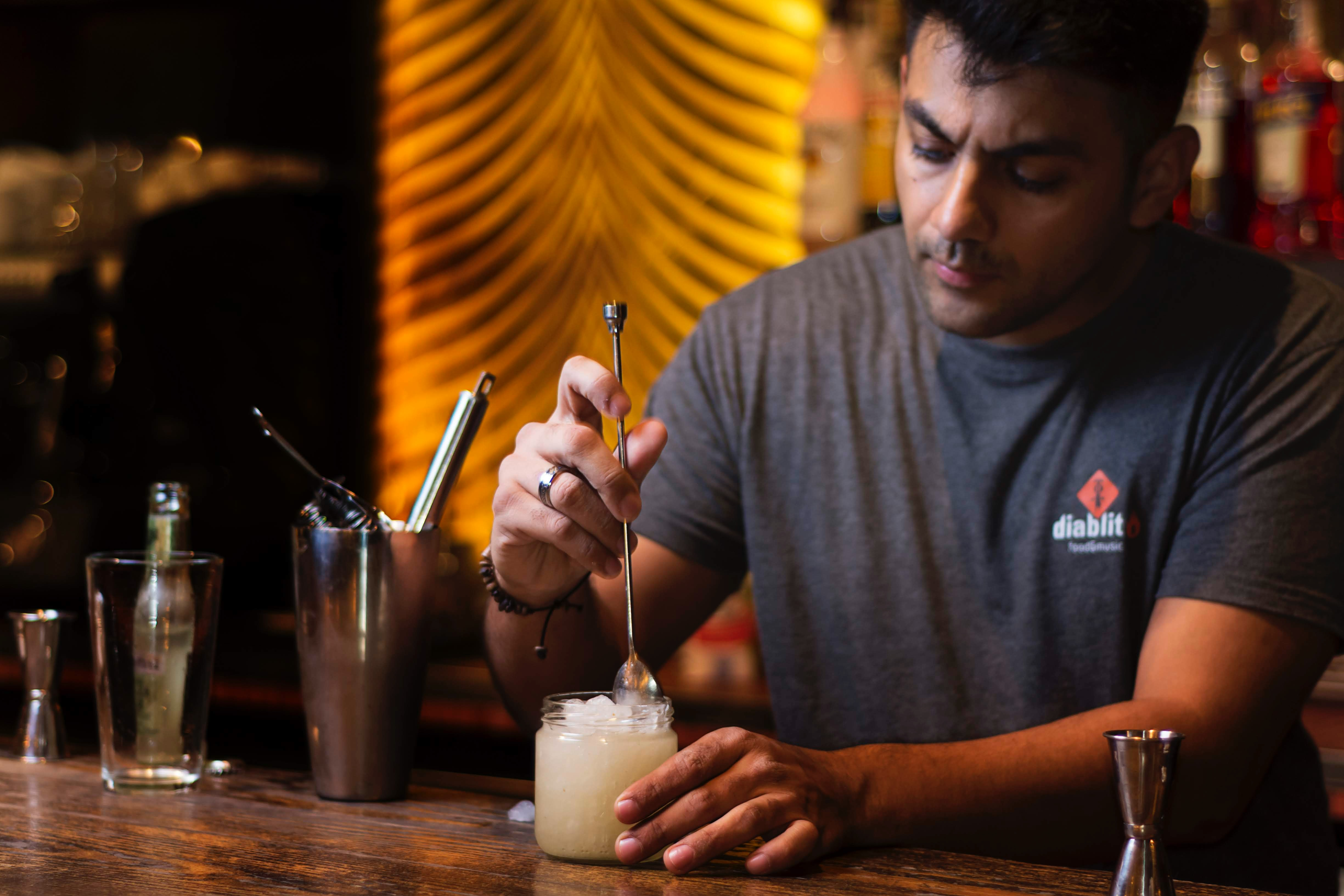 Bartender using a bar spoon to stir cocktail.