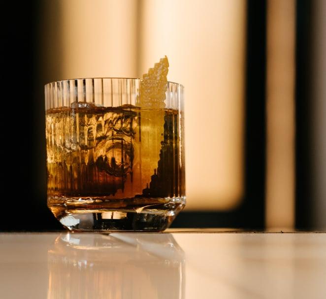 A cocktail with an orange garnish twist.