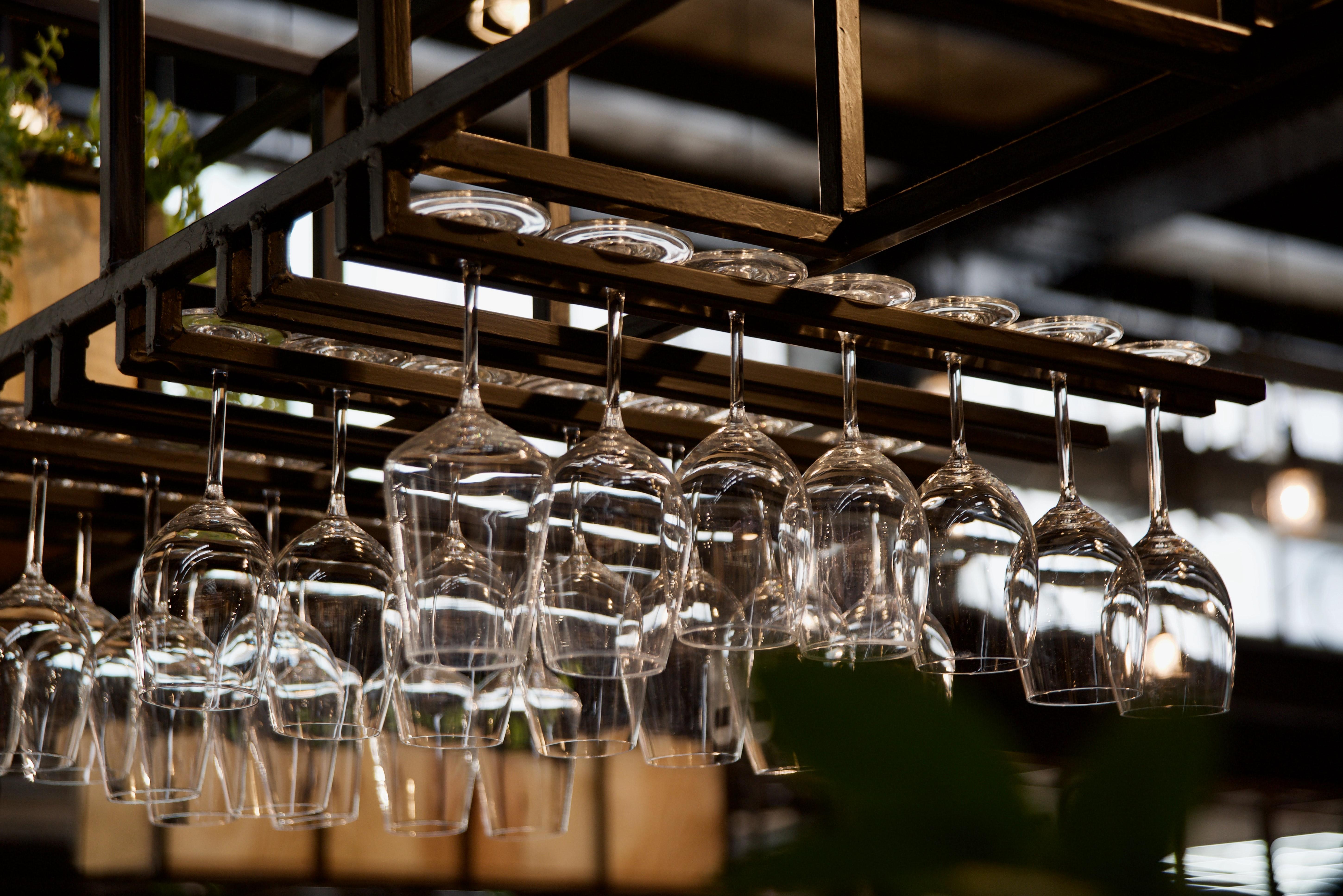 An overhead glass rack of wine glasses.