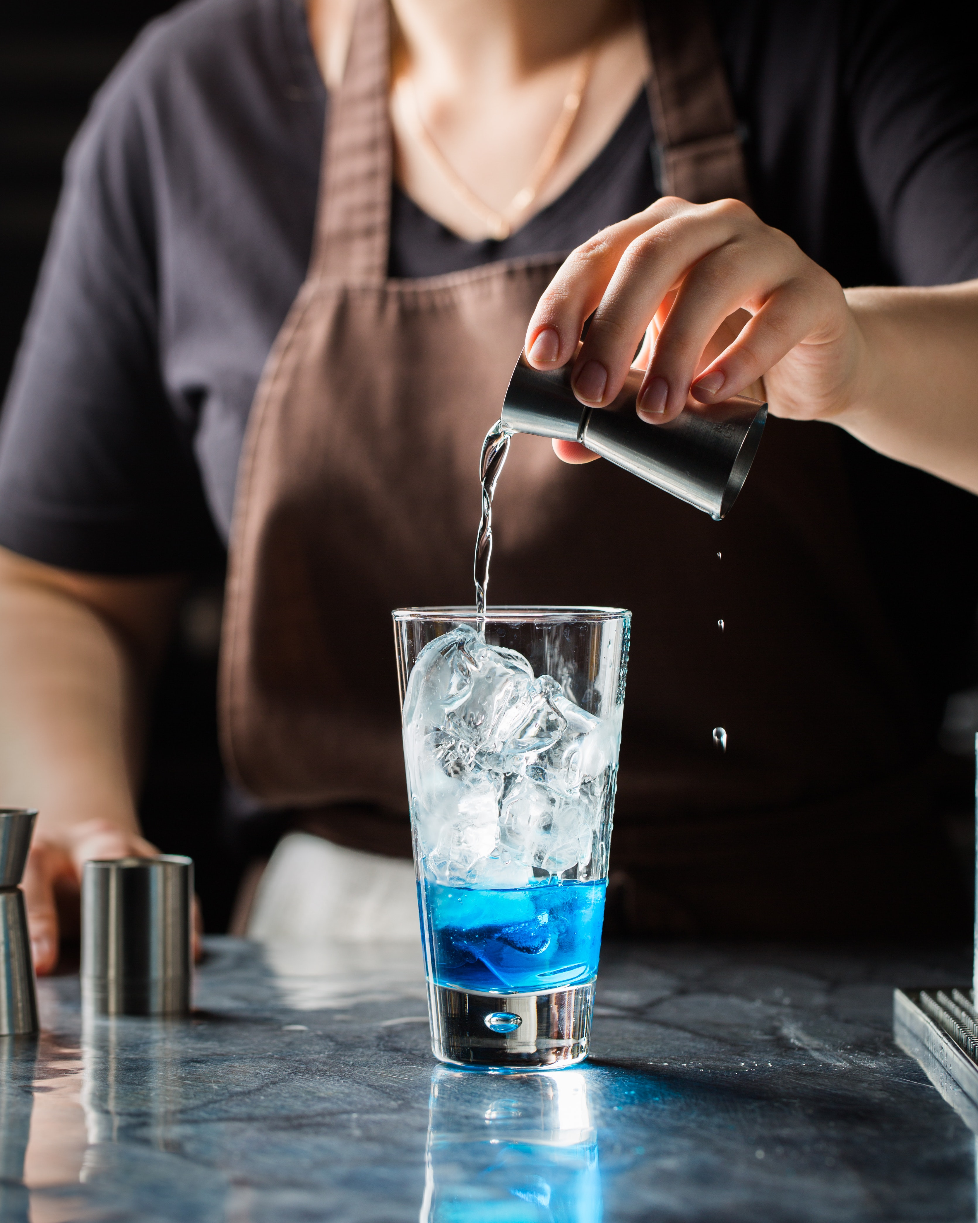 A jigger pouring alcohol into a glass.