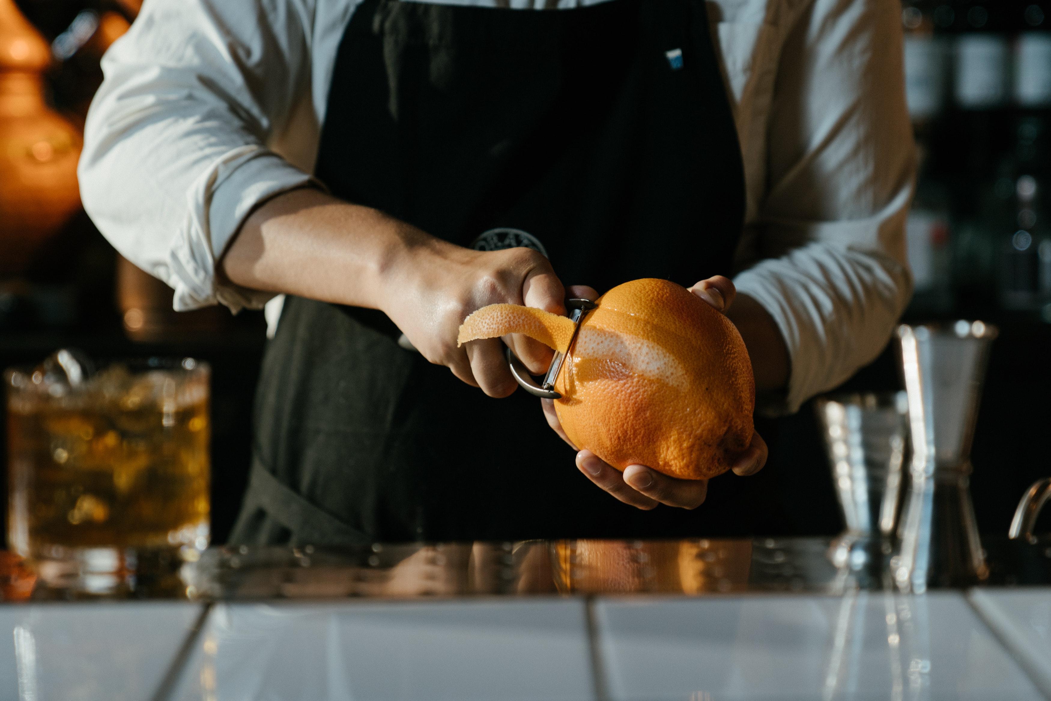 A bartender using a peeler to peel an orange.