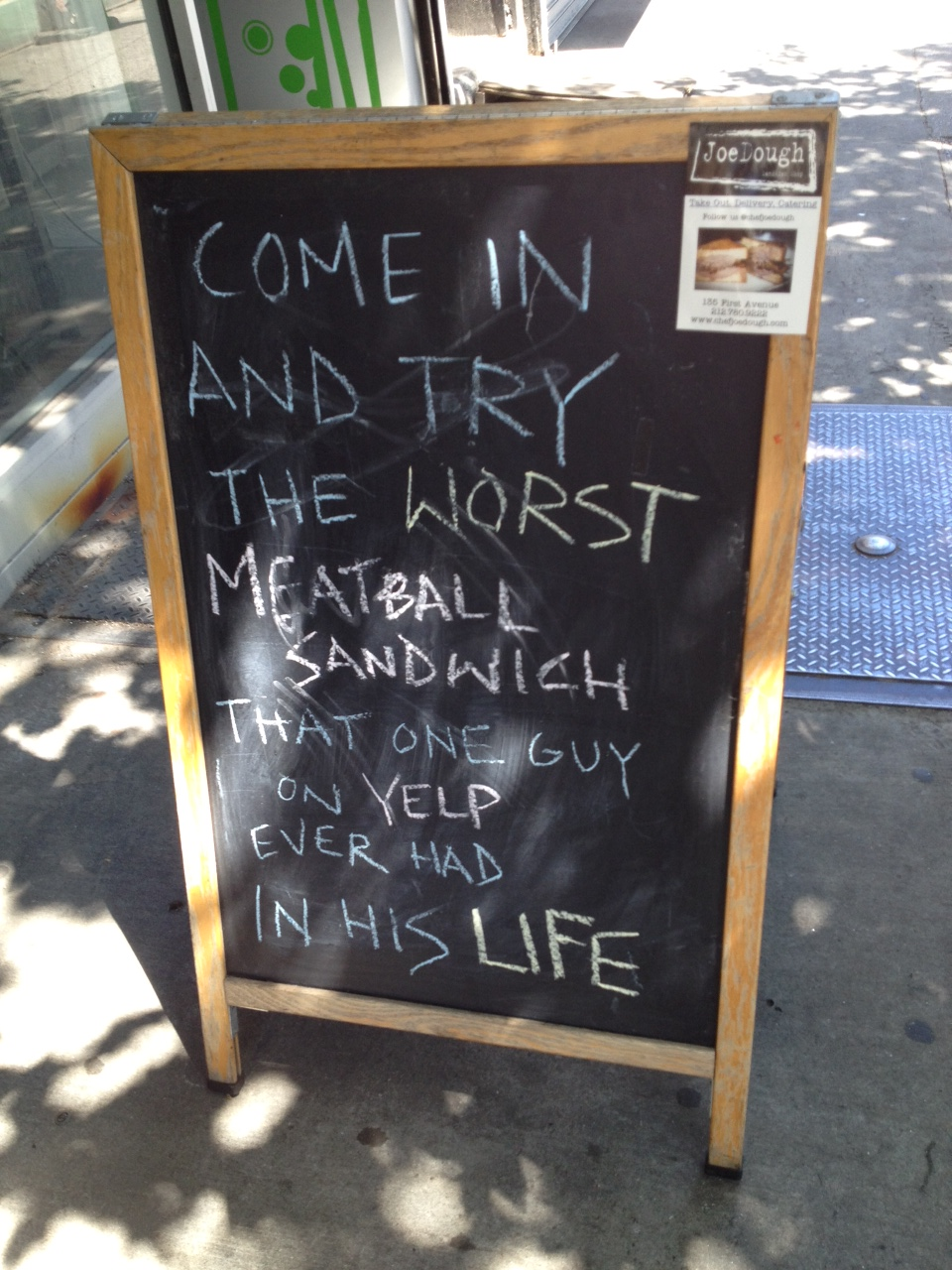 """Chalk sign that reads """"Come in and try the worst meatball sandwich that one guy on Yelp ever had in his life."""""""